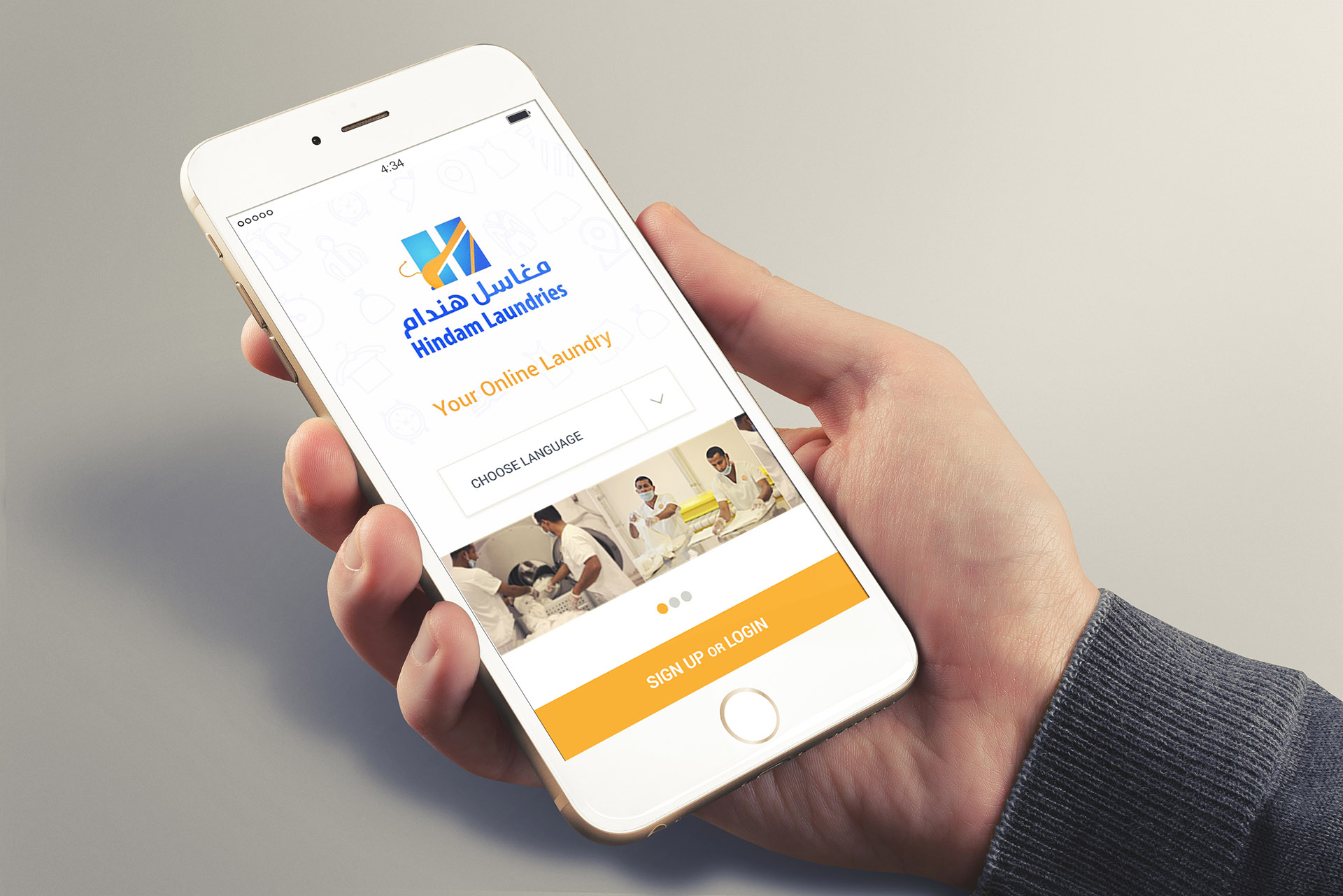 A man holding an iPhone running the Hindam Laundry Application showing the welcome page