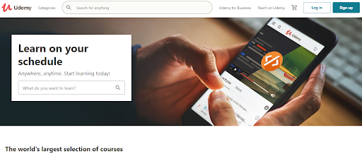a hand holding a mobile opening udemy courses website